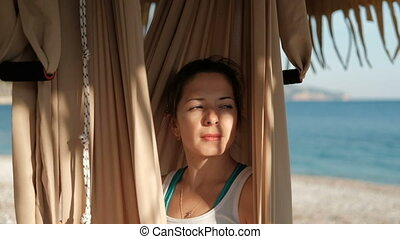On the beach, woman sits in a swinging hammock and looks into distance
