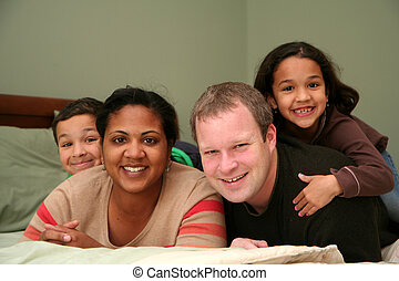 On The Bed - A family laying together on a large bed
