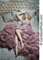 On the big bed is  girl in a magnificent dress.