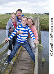On the Bridge - Family of four standing on a bridge and...