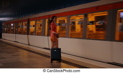 On the business trip - a young modern woman with a suitcase takes her train