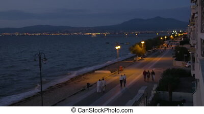 On the coast of city Perea, Greece on evening streets walking people