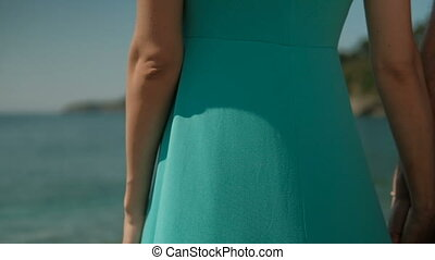 On the coast there is a woman in a turquoise long dress.
