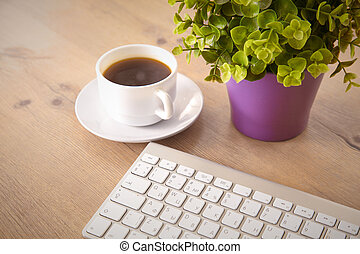 on the desktop computer and a cup of coffee