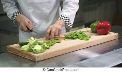 On the desktop, cook in uniform cuts the peppers with a knife.
