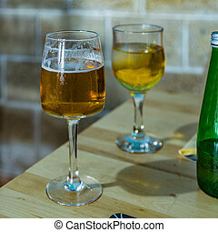 On the dining table is a glass of small foamy beer and a green bottle. Cold gglass of sparkling apple juice with an ice cube on a blurred background. Selective focus, Closeup view. Square frame