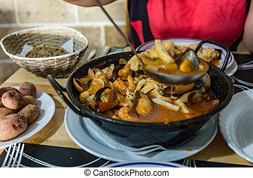 On the dining table is a hot pan with Seafood stew - Zarzuela. horizontal view, closeup. Selective center focus and blurred foreground