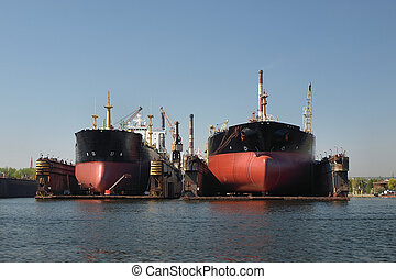 On the dock at the shipyard - A large cargo ship is being...