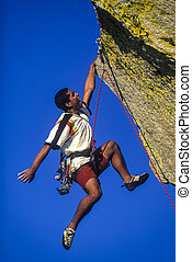 On the edge of danger. - Ethnic climber dangles from his...