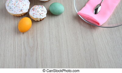On the festive table alongside with painted eggs appears dish and Easter cake.