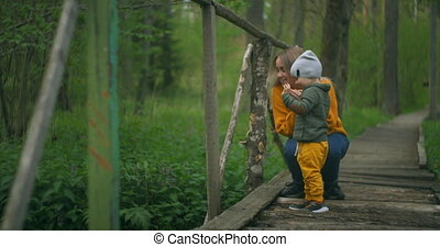 On the forest bridge, mother and son throw stones into the ...