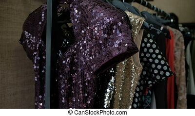 On the hanger hang a dress of sequins that shimmer from the lighting.