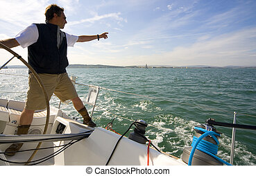 The skipper of a yacht points towards the horizon while keeping one hand on the boat's wheel