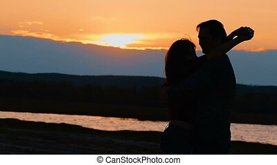 on the lake background hugging woman and a man slow motion video
