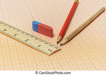 On the millimeter paper are two simple pencils, an eraser and a wooden ruler