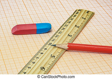 On the millimeter paper lie a ruler, an eraser and a simple pencil close-up