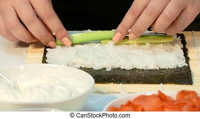 On the nori sheet, lay the cucumber and cheese