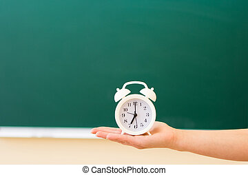 On the palm hand, against the blackboard, is a white alarm clock. Back to school concept.