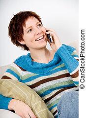 On the phone - cute girl on the phone on the sofa