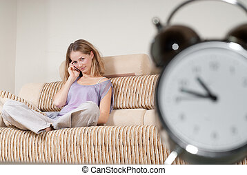 Young woman is sitting on sofa and talking via mobile phone for hours