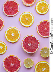 On the pink background lie juicy and ripe slices of orange, lemon and grapefruit