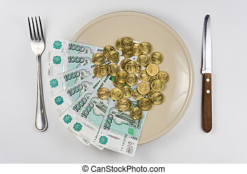 On the plate is a bunch of Russian ten-thousandths of bills and coins lay near cutlery, top view