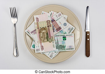 On the plate is a lot of money Russian rubles, lie next to utensils top view