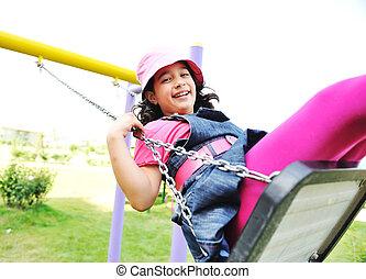 On the playground, swinging
