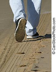 Man walking on tire tracks