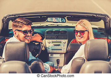On the road to adventures. Happy young couple smiling and looking at camera while riding in their convertible
