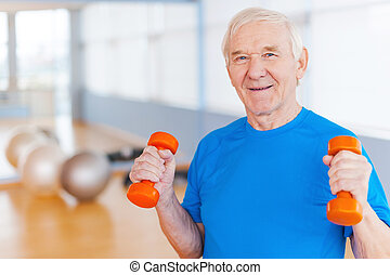 On the road to recovery. Happy senior man exercising with dumbbells and smiling while standing indoors