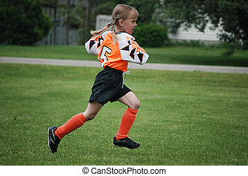 On The Run - Young soccer player running on the field.