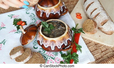 On the russian table is pot with lenten meal. Hand adds pepper to the soup.