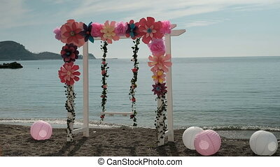 On the seashore swing empty swings decorated with flowers and balls.