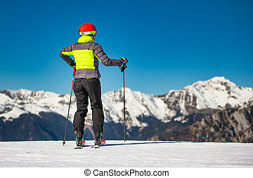 On the ski slopes of a ski area, a skier looks at the mountains before skiing