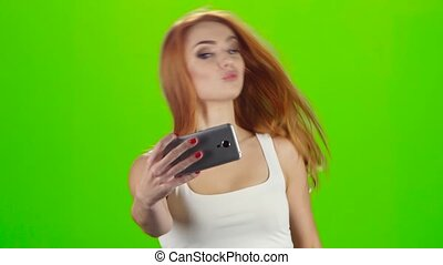 On the smartphone camera redhead girl doing selfie. Green screen