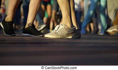 On the street dance floor close-up legs of dancing people.