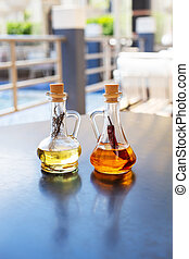 On the table are two glass bottles filled with spicy and ...