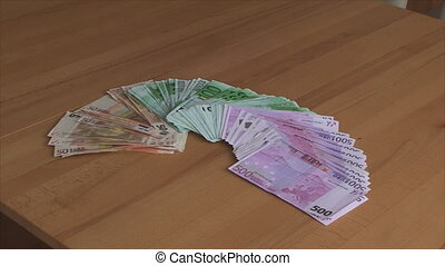 On the table in the room Euro banknotes of different denominations spread out by a fan