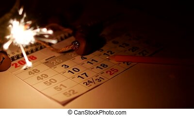 On the table is a calendar with holiday dates New Year's...