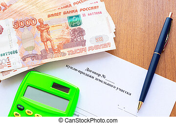 On the table is a contract for the sale of a land plot, a bundle of money, a calculator and a pen