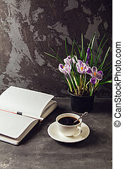 On the table is a Cup of coffee and a vase with flowers crocuses and a blank Notepad