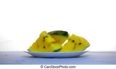 On the table slices of yellow watermelon. Another slice falls from above