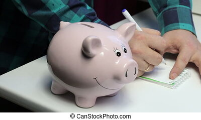 On the table there is a piggy bank in the form of a pink pig. A man puts a coin in it, makes notes in a notebook.