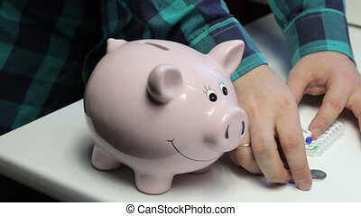 On the table there is a piggy bank in the form of a pink pig. A man puts in her coins, makes notes in a notebook.