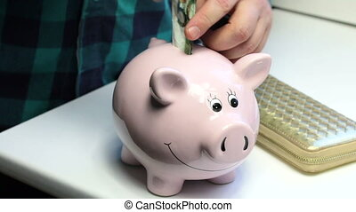 On the table there is a piggy bank in the form of a pink pig and a purse. The man pushes the paper bill into the piggy bank and picks up the wallet.