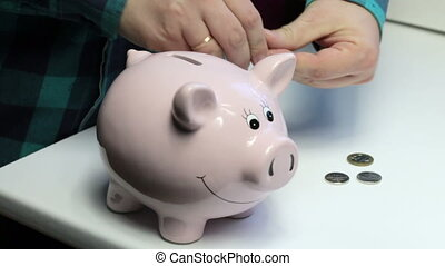 On the table there is a piggy bank in the form of a pink pig. Lying scattered coins. A man collects coins from the table and puts them in a piggy bank.
