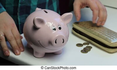 On the table there is a piggy bank in the form of a pink pig. Lying wallet and scattered coins. A man collects coins from the table and puts them in a piggy bank.