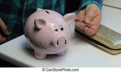 On the table there is a piggy bank in the form of a pink pig. Lying wallet and scattered coins. A man collects coins from the table, puts them in a piggy bank and closes the wallet.