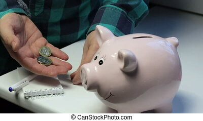 On the table there is a piggy bank in the form of a pink pig. The man from the coin table, throws them into the piggy bank. Makes notes in a notebook.